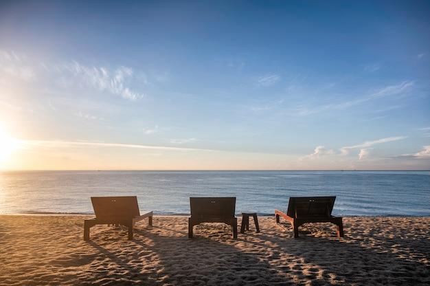 Três espreguiçadeiras de madeira com sol na praia em um mar tropical no verão