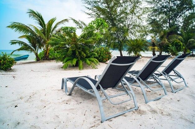 Três espreguiçadeiras ficam na areia branca contra o céu azul e o mar límpido com águas azul-turquesa. o conceito de recreação no resort. bela paisagem exótica com natureza asiática