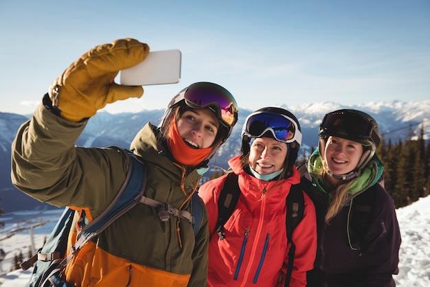 Três esquiadoras tirando selfie no celular