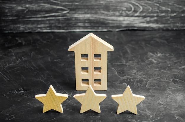 Três estrelas de madeira e uma casa. hotel de três estrelas ou restaurante. revisão do crítico.