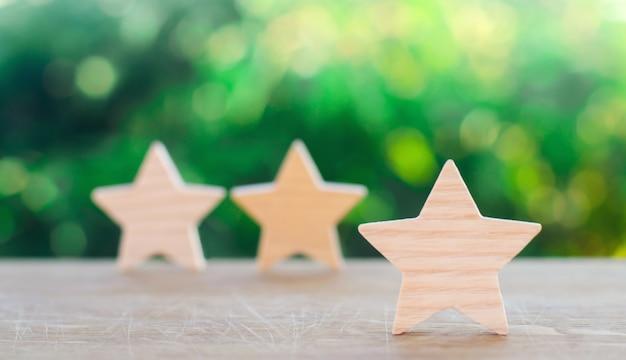 Três estrelas de madeira sobre um fundo verde bokeh.