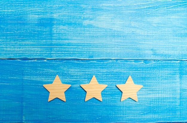 Três estrelas em um fundo azul. o conceito de classificação e avaliação.