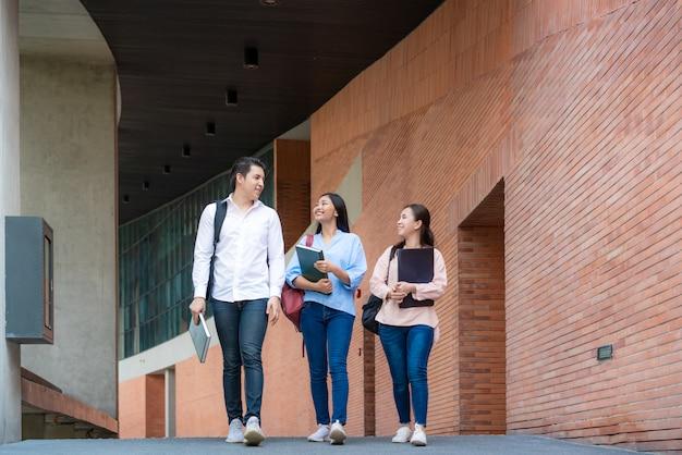 Três estudantes asiáticos estão andando e conversando