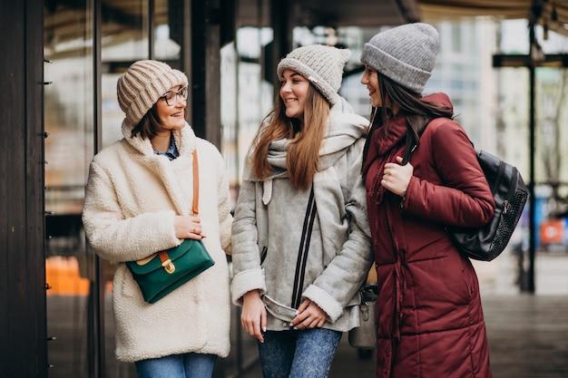 Três estudantes com roupa de inverno na rua