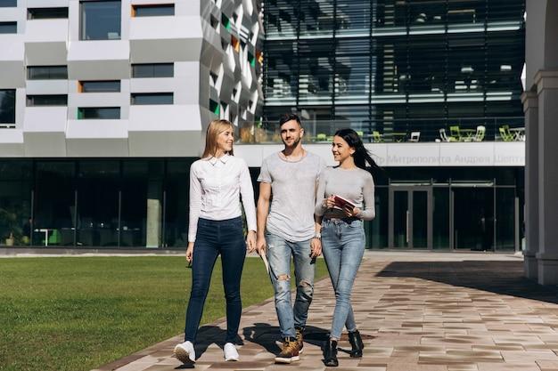 Três estudantes conversam caminhando da universidade