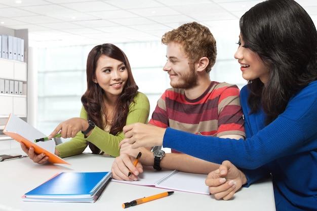 Três estudantes multiculturais, estudando juntos