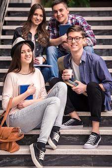 Três estudantes novos que aprendem em escadas na faculdade.