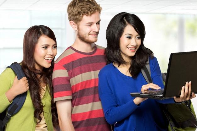 Três estudantes olhando para um laptop