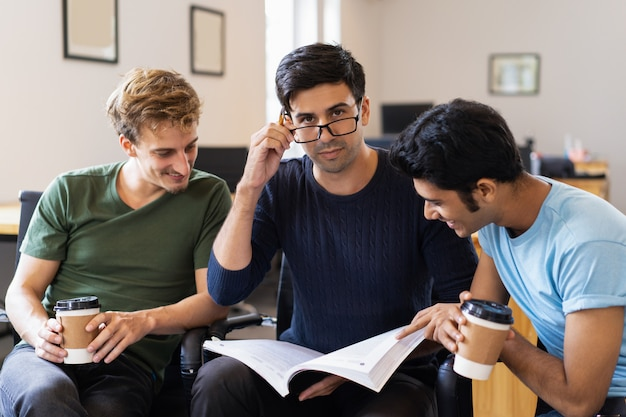 Três estudantes positivos estudando juntos e bebendo