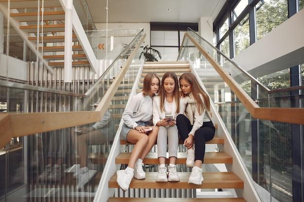 Três estudantes sentados em uma escada com um telefone