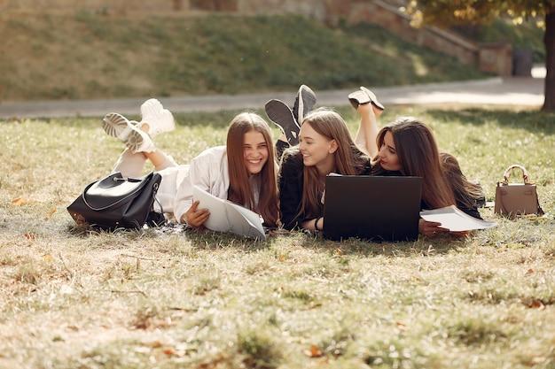 Três estudantes sentados em uma grama com laptop