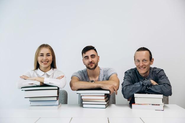 Três estudantes sentam-se à mesa com livros em sala branca