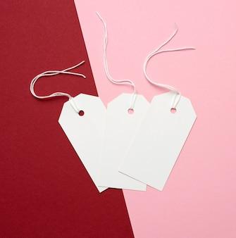 Três etiquetas retangulares de papel branco em uma corda em um fundo colorido