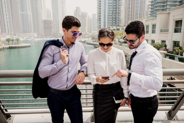 Três faculdades de negócios ocupadas apoiadas na cerca e olhando para o telefone