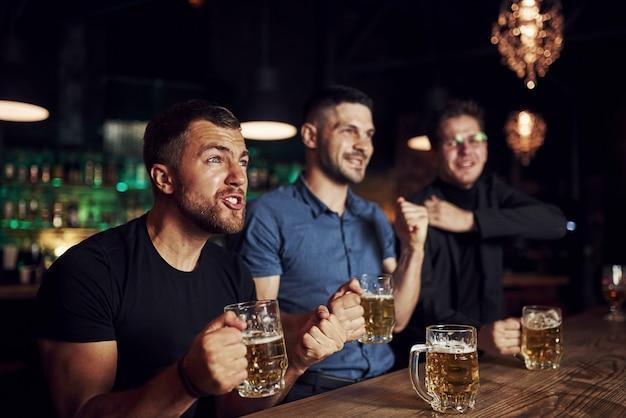 Três fãs de esportes em um bar assistindo futebol. com cerveja nas mãos.