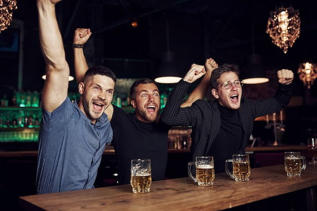 Três fãs de esportes em um bar assistindo futebol