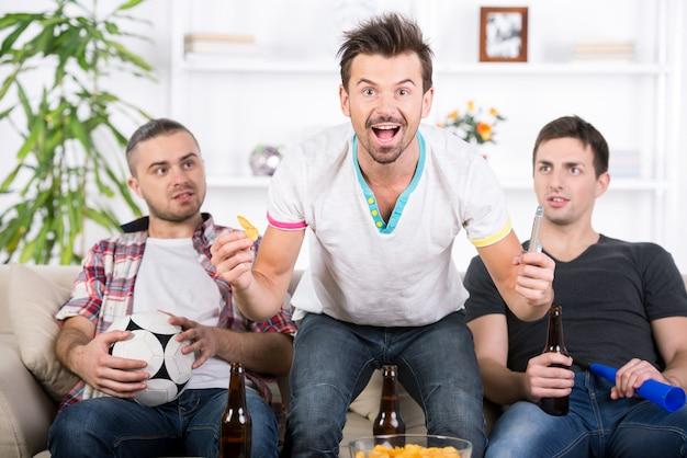 Três fãs de futebol estão torcendo jogo de futebol em casa.