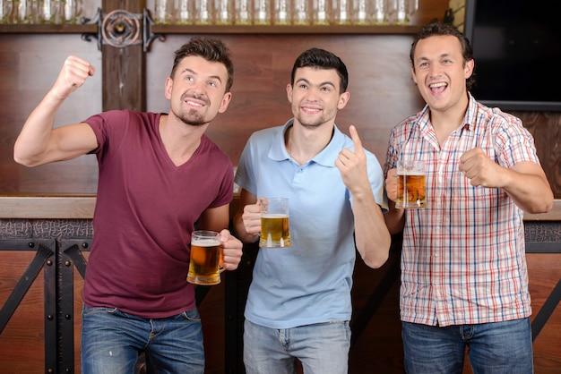 Três fãs de futebol felizes que bebem a cerveja no bar.