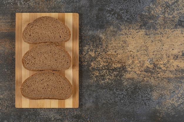 Três fatias de pão preto na placa de madeira.