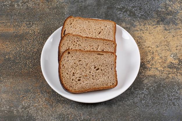 Três fatias de pão preto no prato branco