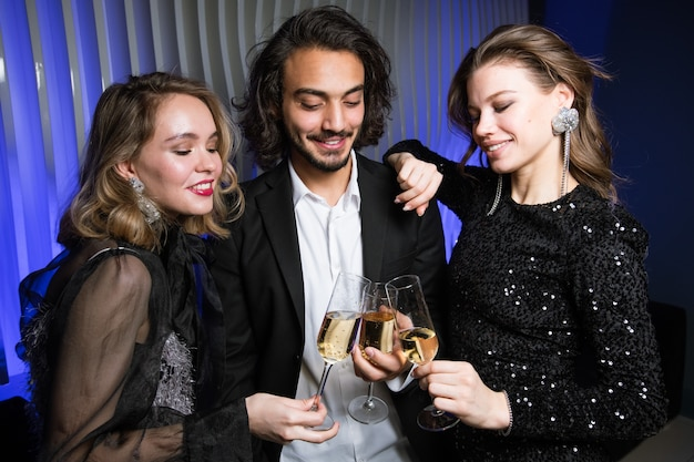 Três felizes amigos bem vestidos brindando com taças de champanhe na boate enquanto aproveitam a festa