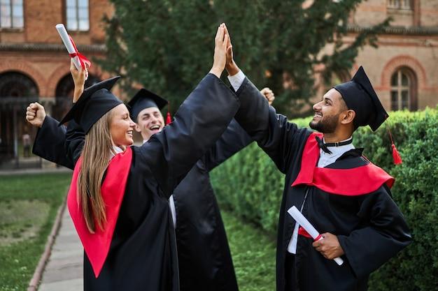 Três felizes amigos internacionais de pós-graduação cumprimentando no campus da universidade com vestes de formatura com diploma.