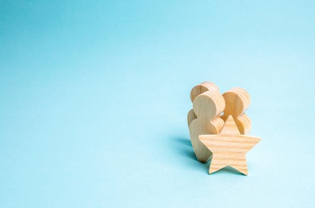 Três figuras de madeira de pessoas e uma estrela. sinal de diferença, avaliação positiva