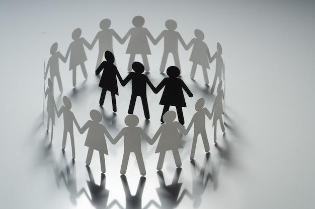 Três figuras humanas de papel rodeadas por um círculo de pessoas de papel de mãos dadas