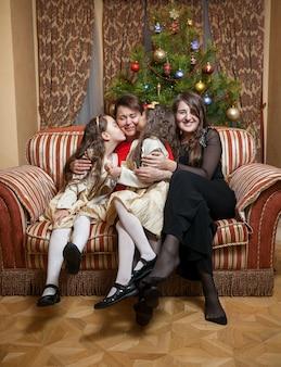 Três filhas felizes sentadas no sofá com a mãe no natal