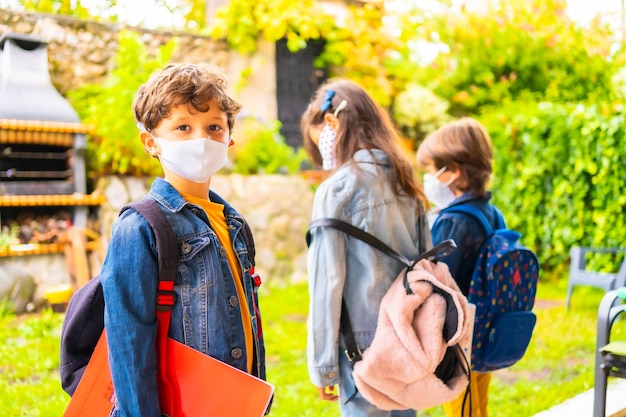 Três filhos irmãos com máscaras prontas para voltar à escola. nova normalidade, distância social, pandemia de coronavírus, covid-19.