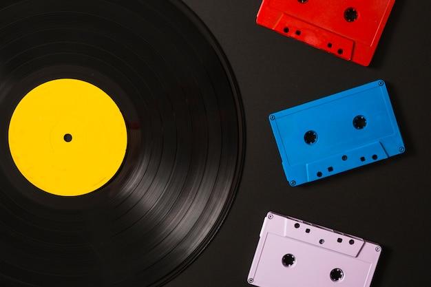 Três fitas cassete e discos de vinil em fundo preto