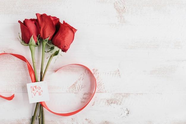 Três flores vermelhas com cartão de amor e espaço de cópia