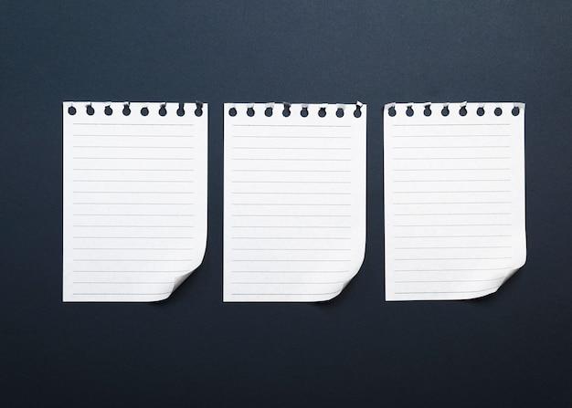 Três folhas de papel branco em branco, rasgadas de um bloco de notas