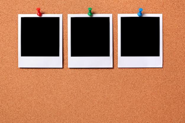 Três fotos do polaroid impressões fixadas a uma placa de observação da cortiça