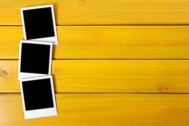 Três fotos do polaroid impressões sobre uma mesa de madeira ou mesa