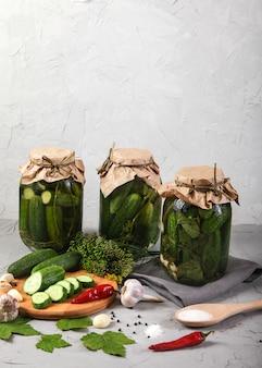 Três frascos com pepinos fermentados, pepinos picados em uma placa, pimenta, alho e sal em um concreto.