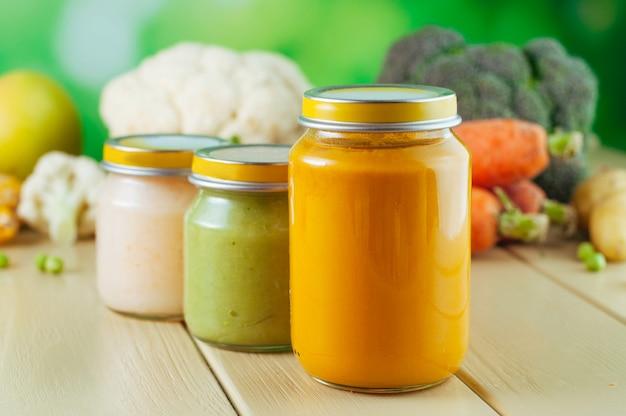 Três frascos com purê de frutas e vegetais