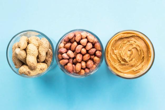 Três frascos de amendoim em uma casca, ervilhas descascadas e manteiga de amendoim vegan