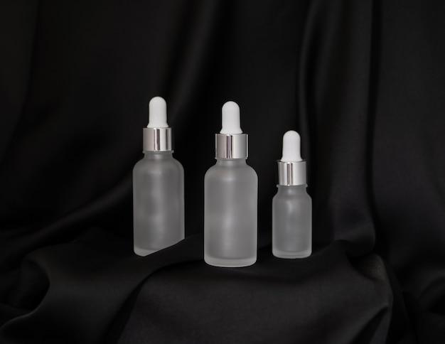 Três frascos de cosméticos lado a lado em um fundo de seda preta