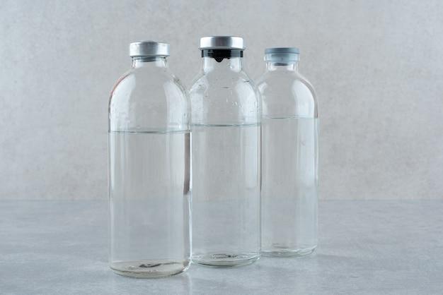 Três frascos de etanol medicinal em fundo cinza. foto de alta qualidade