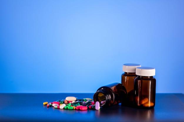 Três frascos de remédios de plástico marrom com uma tampa de rosca de pé sobre um fundo azul ao lado de um punhado de comprimidos