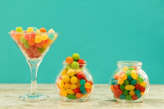 Três frascos de vidro cheios de jellybeans com fundo azul