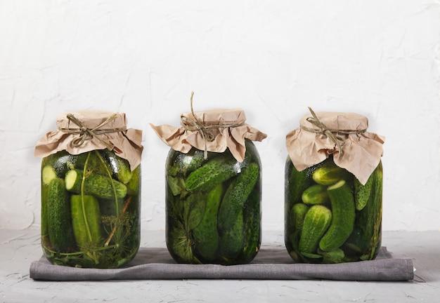 Três frascos de vidro grandes com pepinos fermentados estão em um guardanapo cinza contra um concreto.