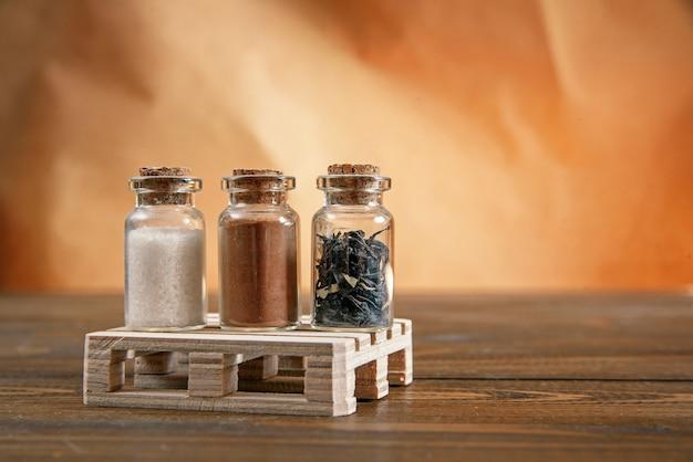 Três frascos pequenos cheios de açúcar, canela e chá em um suporte de madeira em cima da mesa