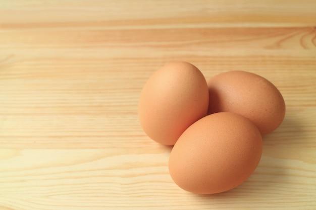Três, fresco, cru, ovos galinha, isolado, ligado, a, tabela madeira
