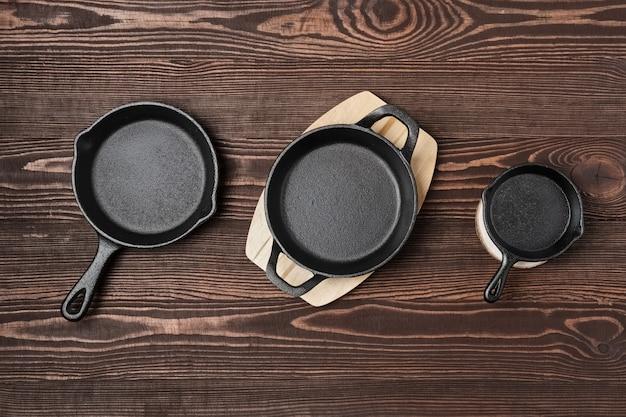 Três frigideiras de ferro fundido mini vazia na mesa de madeira, vista de cima