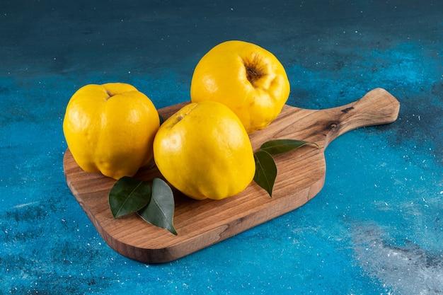 Três frutas frescas de marmelo com folhas colocadas em uma tábua de madeira