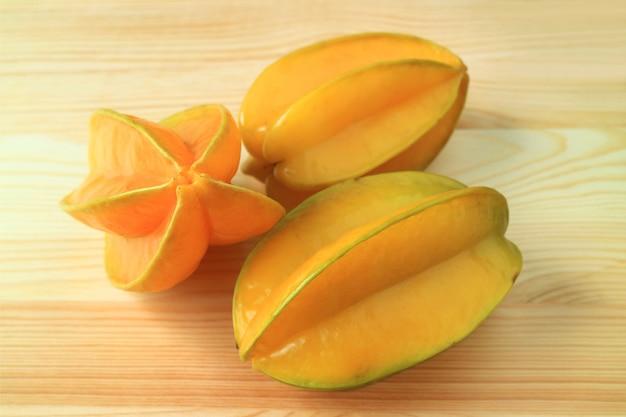 Três frutas inteiras maduras amarelas vívidas de star fruit isoladas na mesa de madeira natural