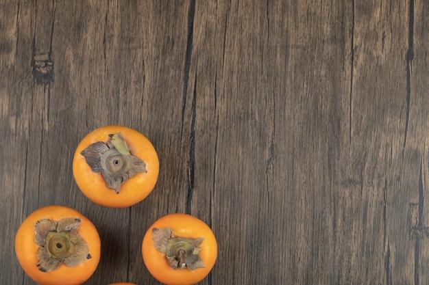 Três frutas maduras de caqui colocadas em superfície de madeira