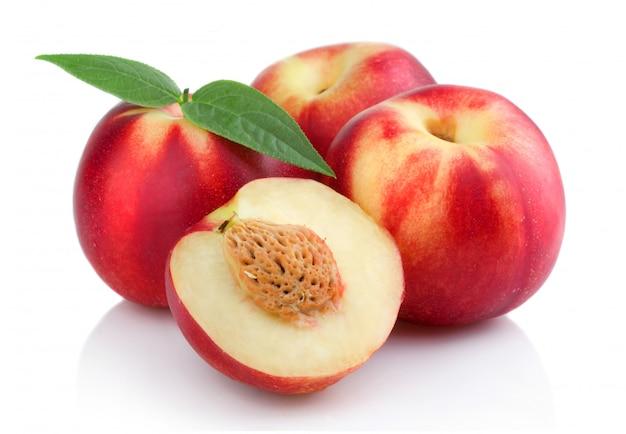 Três frutas maduras de pêssego (nectarina) com fatias isoladas